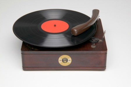 An antique record player with a record playing.