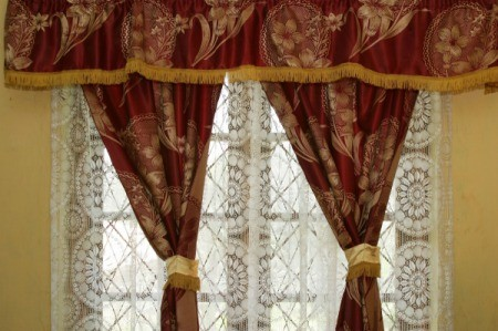 Ornate dry clean only drapes hanging in a window.