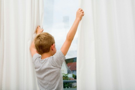 A boy holding onto white curtains as he looks out the window.