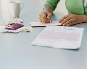 A woman writing checks to pay bills.