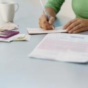 A woman writing checks to pay bills.