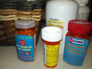 Several bottles of prescriptions on a counter.