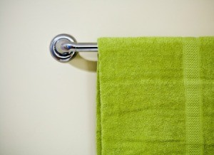 A towel rack with a green towel hanging on it.