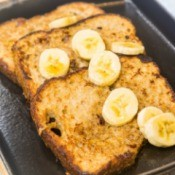 French toast slices in a pan with banana slices.
