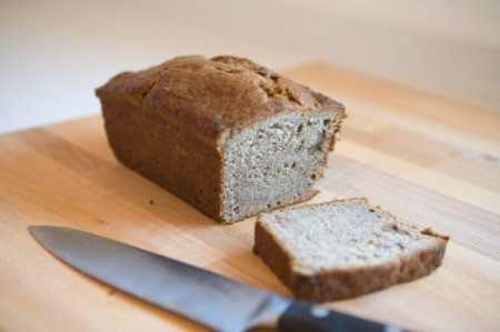 A loaf of banana bread with a slice cut out of it.