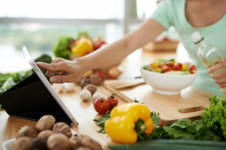 A woman reading a recipe off a tablet, preparing a healthy meal.