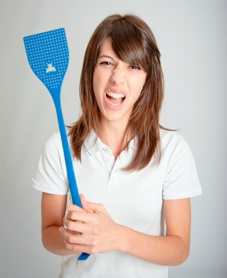 A woman holding a blue fly swatter.