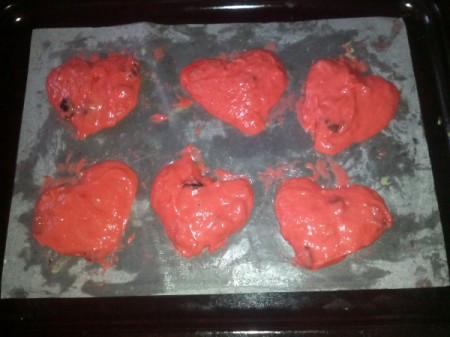 heart shaped red cookies on baking pan