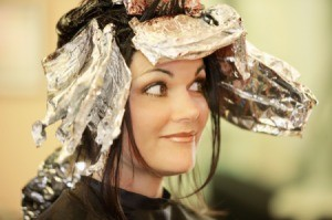 A dark haired woman getting a foil treatment at a salon.