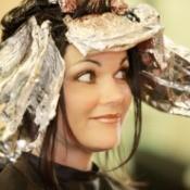 A dark haired woman getting a foil treatment at a salon.