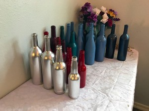 Rows of different colored painted wine bottles.