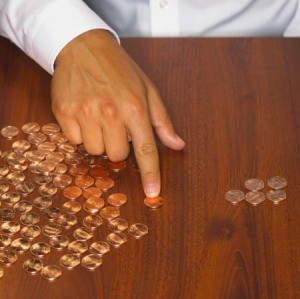 A hand counting pennies on a wooden desk.