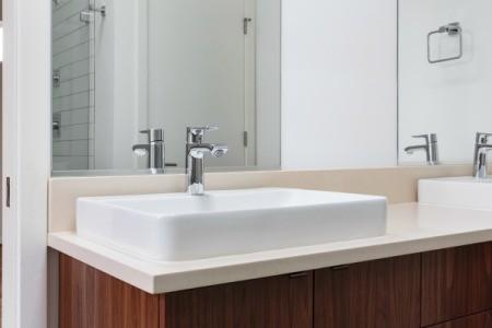 A plain bathroom mirror over a sink.