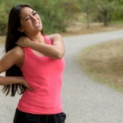 A runner with a muscle cramp in her shoulder.