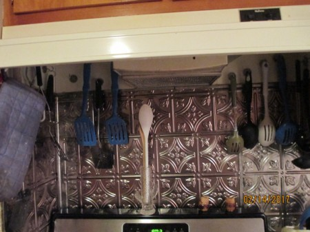 Kitchen Implements Organized - hanging from cup hooks on stove vent
