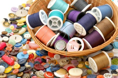 A basket of thread on a background of buttons.
