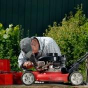A man repairing a lawn mower.