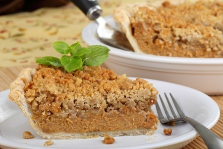 A slice of pumpkin pie with streusel topping.
