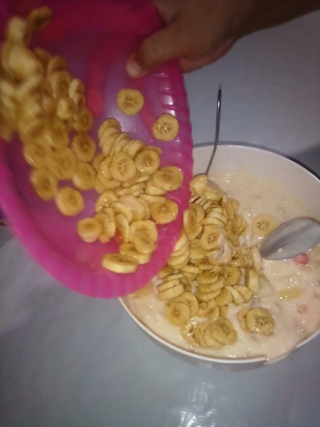 adding banana slices to bowl
