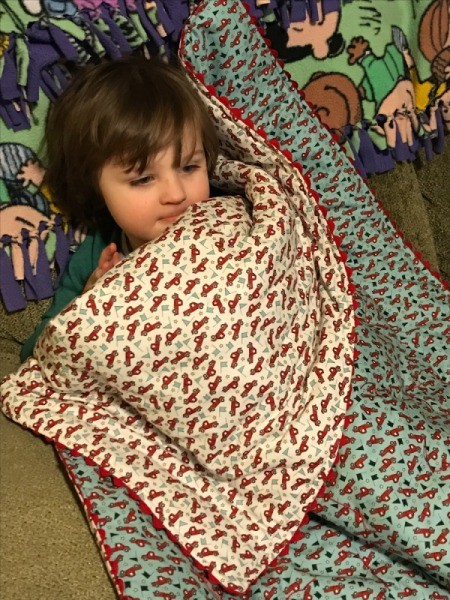 Whole Cloth Tied Quilt with Ric Rac Trim - child under quilt