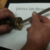 Using a hacksaw to remove a broken key in a lock.