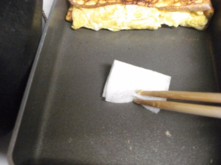 oiling pan with omelet at one end