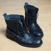A pair of boots with black rubber soles on a wood floor.