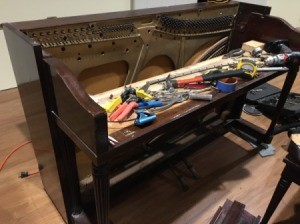 An upright piano being used as a desk.