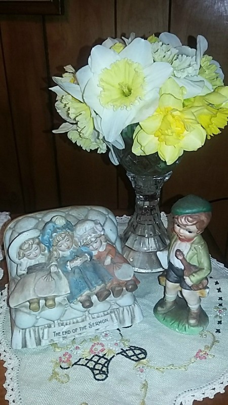 A vase with yellow daffodils next to some figurines.