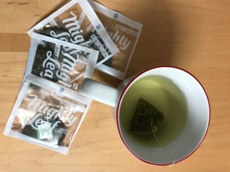 Tea bags next to a cup of tea.