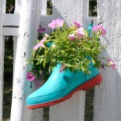 Shoe planter attached to a fence.