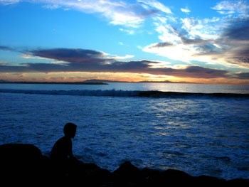 A boy silhouetted in front of the ocean at sunset.