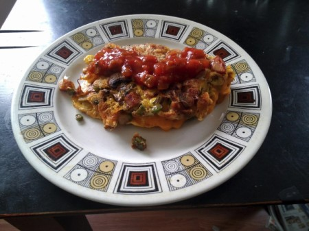 Omelet covered with salsa on plate