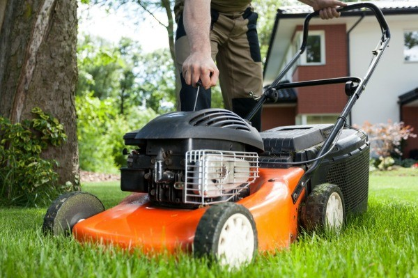 A Man Pulling The Starter Cord For Lawn Mower