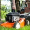 A man pulling the starter cord for a lawn mower.