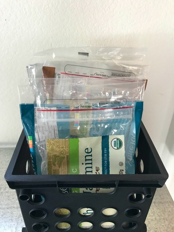 Pantry supplies organized in a plastic crate.
