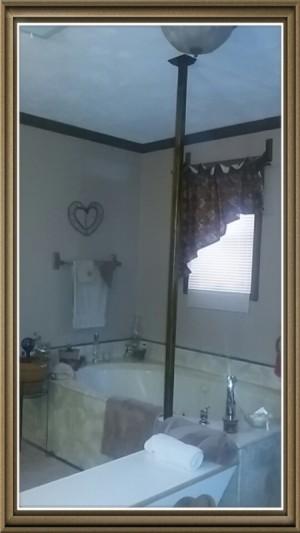 A bathtub with a pole for gripping.