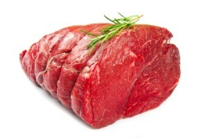 An uncooked beef roast with a sprig of rosemary on top.