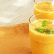 Two orange colored smoothies in glasses.
