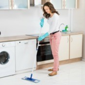 A woman cleaning a laminate floor.