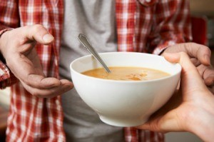 A bowl of soup being handed to a hungry person.