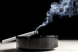 Smoke rising from a cigarette in an ashtray.