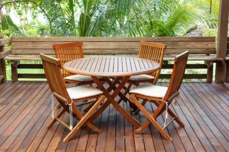 A teak wood deck with teak wood furniture on it.