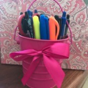 A pink tin pail filled with pens and markers on a desk.