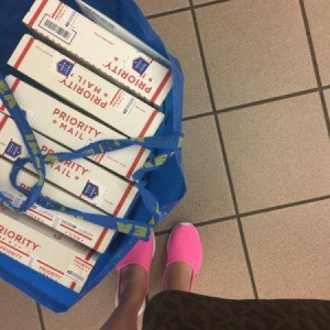 A large shopping bag full of mail packages.