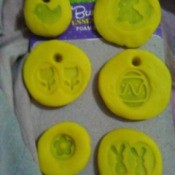 Play-Doh Stamping Activity for Children - circles of yellow Doh with various stamped images and some with holes to hang