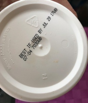 An expiration date on the bottom of a container.