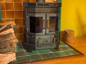 A wood stove with blackened windows.