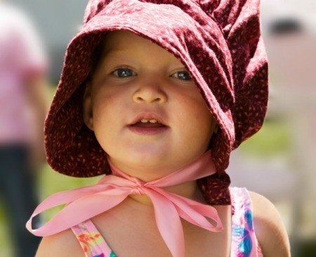 A little girl wearing a pioneer bonnet.