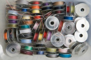 A box full of sewing bobbins with different colored thread.